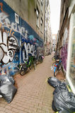 Amsterdam. Bicycles, graffiti and trash bags in a narrow alley in Amsterdam Stock Image