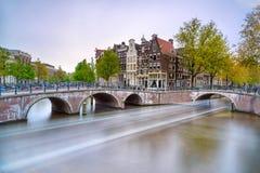 Amsterdam. Brücken- und Wasserkanal. Bootslichtspur auf Sonnenuntergang. Holland oder die Niederlande. Stockfotos