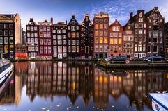 Amsterdam byggnads fasad med reflexionen i kanal, afton (skjuten lång exponering) arkivbild