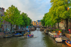 Amsterdam canal with the boat rowers  Royalty Free Stock Images