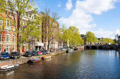 Amsterdam canal with boats along the bank of the river in the spring. Netherlands. Stock Image