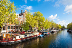 Amsterdam canal with boats along the bank of the river during the sunny day, Netherlands. Stock Images