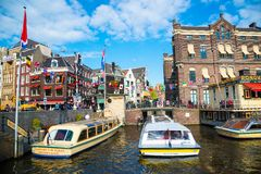 Amsterdam canal with boats on the background of traditional houses royalty free stock images