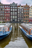 Amsterdam canal. Canal boats in Amsterdam wait to carry tourists for site seeing along the city canals Royalty Free Stock Image