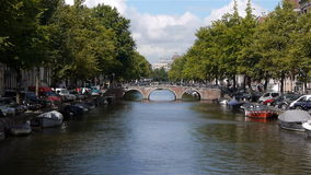 Amsterdam canal with bridge, boats, cars and bikes. Long shot of a canal and bridge in Amsterdam with boats, cars and bikes stock footage