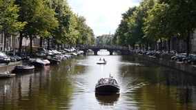 Amsterdam canal with bridge and boats. Long shot of a canal and bridge in Amsterdam. Boats are passing by stock footage
