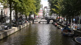 Amsterdam canal with bridge, in the historical centre. Long shot of a canal and bridge in the historical centre of Amsterdam stock video
