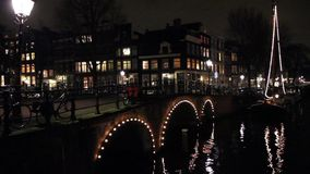 Amsterdam canal and bridge at night stock video