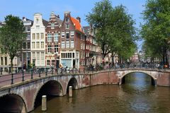 Amsterdam canal crossing. AMSTERDAM, NETHERLANDS - JULY 7, 2017: Tourists visit Keizersgracht and Leidsegracht canal crossing in Amsterdam, Netherlands Royalty Free Stock Photos