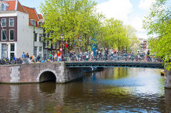 Amsterdam canal with crowd of people and bikes along the bridge during King's Day. Stock Photo