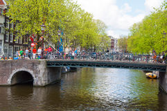 Amsterdam canal with crowd of people and bikes on the bridge. Royalty Free Stock Photo