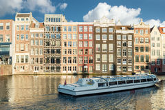 Amsterdam canal cruise ship with Netherlands traditional house Royalty Free Stock Photography