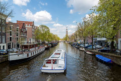 Amsterdam canal cruise ship with Netherlands traditional house i Stock Photography