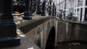 Amsterdam canal, early morning, cloudy day, Autumn, details - bridge, bicycles, tourists Stock Photo