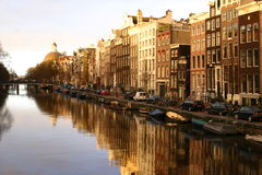 Amsterdam canal. Evening sun in Amsterdam gives pretty reflections of a typical street scene Stock Photography