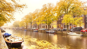 An Amsterdam canal in the Fall. Houses, boats and a canal in Amsterdam, photographed on a foggy morning during the autumn season Stock Photo