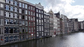 Amsterdam canal with historic houses. Perspective shot of a canal in Amsterdam with historic houses stock footage
