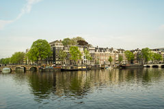 Amsterdam canal houses on a sunny day. Amsterdam canal scene with typical historical buidings and boats floating Stock Images