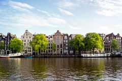 Amsterdam canal houses on a sunny day. Amsterdam canal scene with typical historical buidings and boats floating Stock Photos