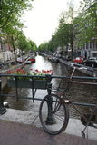 An Amsterdam canal lined with boats and buildings. A typical Amsterdam canal seen from a scenic bridge with flowers and an old bicycle in the foreground Stock Images