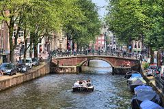 Amsterdam canal. AMSTERDAM, NETHERLANDS - JULY 7, 2017: People visit Leidsegracht canal in Amsterdam, Netherlands. Amsterdam is the capital city of The Stock Image