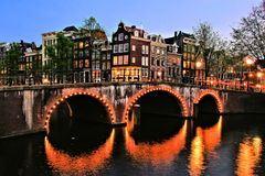 Amsterdam canal night scene. Canal houses of Amsterdam with bridge lit at night, Netherlands Royalty Free Stock Photography