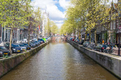 Amsterdam canal with parked cars along the bank. Royalty Free Stock Photos