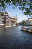 Amsterdam canal / river boat scene. Looking down a large canal in Amsterdam. Portrait rotation scene on a sunny day Royalty Free Stock Images