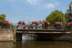 Amsterdam canal scene with bicycles and bridges Stock Photography