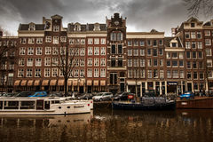 Amsterdam canal scenery. With boats crossing the water. Traditional narrow red tinted houses in the background Royalty Free Stock Image