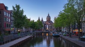Amsterdam canal and skyline at night with Saint Nicholas Church time lapse in Amsterdam city, Netherlands