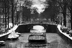Amsterdam canal tour boat BW. Beautiful view of a canal boat under a bridge at the famous UNESCO world heritage canals of Amsterdam, the Netherlands, in black Stock Photo