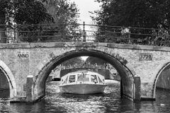 Amsterdam canal tour BW. Beautiful view of a canal boat under a bridge at the famous UNESCO world heritage canals of Amsterdam, the Netherlands, in black and Royalty Free Stock Photos