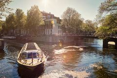 Amsterdam canal with tourist boat Stock Images