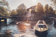 Amsterdam canal with tourist boat stock photography