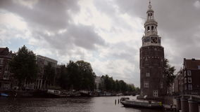 Amsterdam canalboats and Montelbaans Tower timelapse. Timelapse of the Montelbaans Tower in Amsterdam. Canalboats are passing by stock footage
