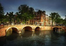 Amsterdam canals with bridge and typical houses Stock Images