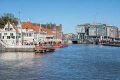 Amsterdam canals with launches and buildings near central railway station royalty free stock image