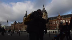 Amsterdam central station front side with moving people and trams. Time Lapse. AMSTERDAM, NETHERLANDS - JANUARY 02, 2017: Amsterdam central station front side stock video footage