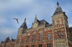 Amsterdam centralstationbyggnad med seagulls Arkivbild