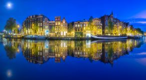 Amsterdam city skyline with moon, Netherlands. Amsterdam city skyline with moon on sky and reflection of houses in river, Netherlands stock photos