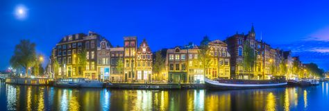 Amsterdam city skyline with moon, Netherlands. Amsterdam city skyline with moon on sky and reflection of houses in river, Netherlands Royalty Free Stock Images