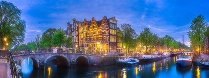 Amsterdam city skyline at night, Netherlands. Amsterdam city skyline with reflection of houses in river at night, Netherlands Royalty Free Stock Image