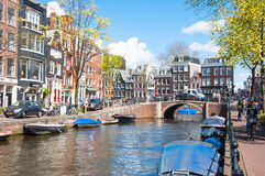 Amsterdam cityscape with row of cars, bikes and boats parked along the Amsterdam canal during the sunny day on April 30,2015. Stock Image