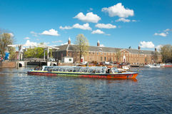Amsterdam cityscape, tourists enjoy canal cruise, Magere Brug also known as Skinny Bridge and Hermitage Amsterdam. Stock Photo