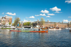 Amsterdam cityscape, tourists enjoy canal cruise, Magere Brug (Skinny Bridge), Hermitage Amsterdam are visible on the background. Stock Photography