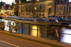 amsterdam cyklar den fartygkanalholland natten Royaltyfri Fotografi