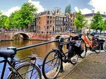 amsterdam cyklar kanalen Arkivfoto