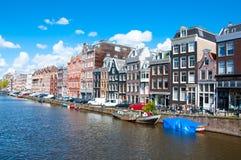 AMSTERDAM 30 DE ABRIL: El paisaje urbano de Amsterdam con la fila de coches, de bicis y de barcos parqueó a lo largo del canal en Imagen de archivo
