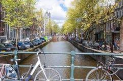 AMSTERDAM, DIE NIEDERLANDE 27. APRIL: Amsterdam-Kanal mit Fahrrädern auf der Brücke und den parkendes Auto entlang der Bank 27,20 Stockfotos